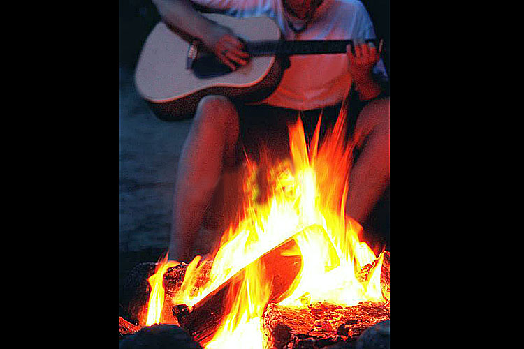 Playing guitar by a bonfire